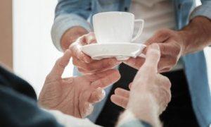 close up van een hulpbehoevende oudere die kop thee/koffie krijgt van zoon